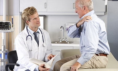 Pain management doctor Examining Male Patient With Shoulder Pain