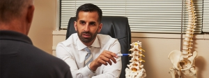 Relievus pain specialist, Dr. Purewal explains lower back and spinal pain symptoms to a patient.